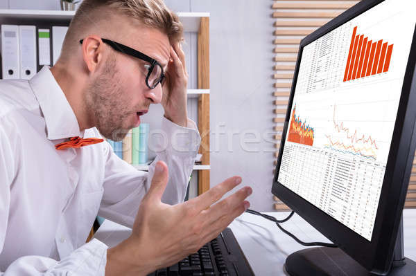 Businessman Looking At Graph Stock photo © AndreyPopov