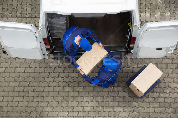 Two Delivery Men Unloading Cardboard Box From Truck Stock photo © AndreyPopov