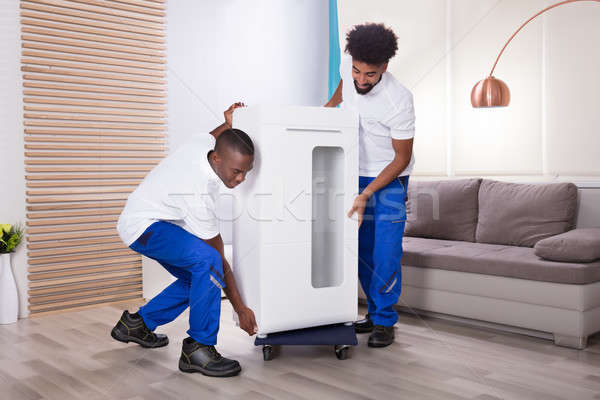Two Male Movers Placing The White Cabinet On Wheel Stock photo © AndreyPopov