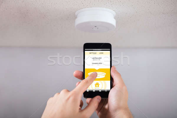 Person Operating Smoke Detector With Mobile Phone Stock photo © AndreyPopov