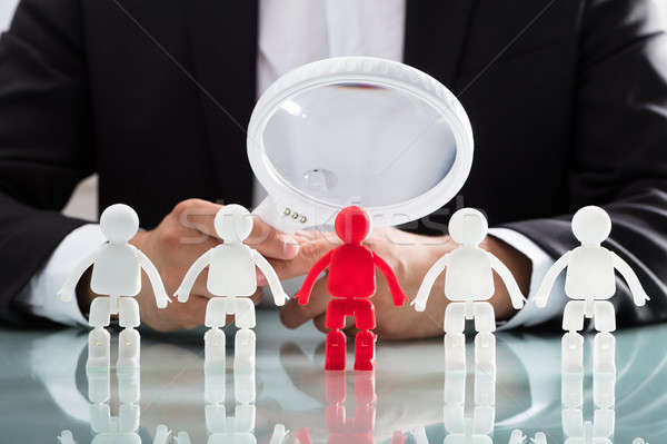Businessperson looking at red figure through magnifying glass Stock photo © AndreyPopov