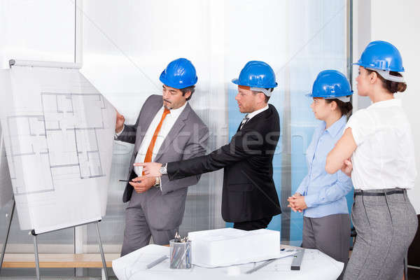 Architects Discussing Plan Drawn On Blueprint At Office Stock photo © AndreyPopov