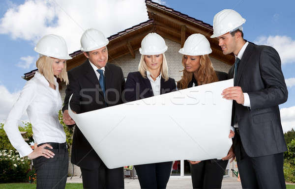 Group Of Architects Holding Blue Print Stock photo © AndreyPopov
