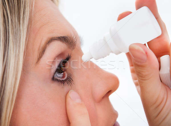 Woman pouring drops in her eyes Stock photo © AndreyPopov