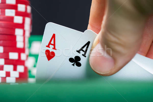 Poker player lifting the corners of two cards Stock photo © AndreyPopov