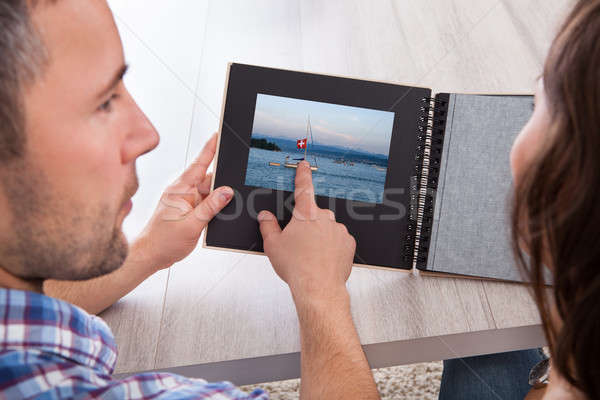 Young Man Pointing On Photo Album Stock photo © AndreyPopov