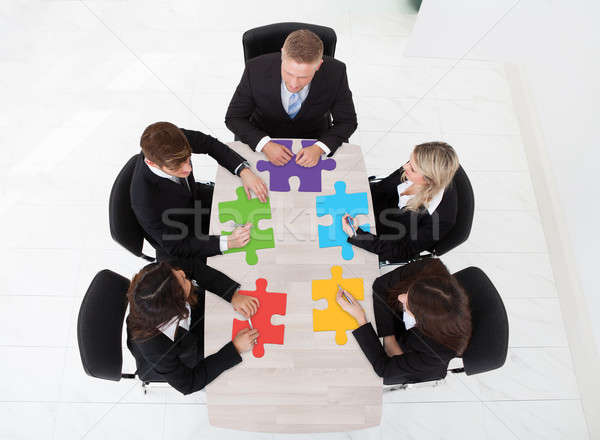 Businesspeople With Jigsaw Pieces Sitting At Table Stock photo © AndreyPopov