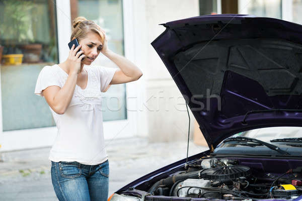 Woman Using Mobile Phone While Looking At Broken Down Car Stock photo © AndreyPopov