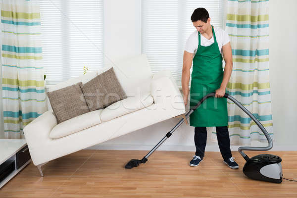 Man Lifting Couch While Cleaning Floor With Vacuum Cleaner Stock photo © AndreyPopov