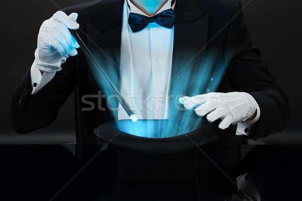 Magician Holding Magic Wand Over Illuminated Hat Stock photo © AndreyPopov