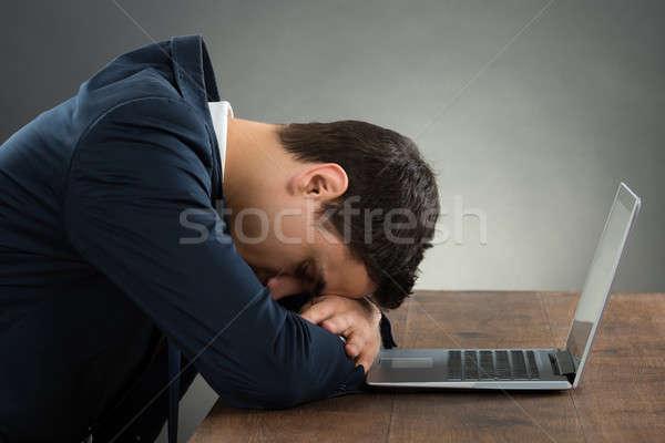 Kimerült üzletember dől asztal oldalnézet laptop Stock fotó © AndreyPopov