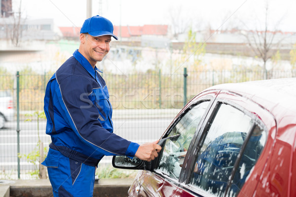 Stock photo: Serviceman Cleaning Car Window At Service Station