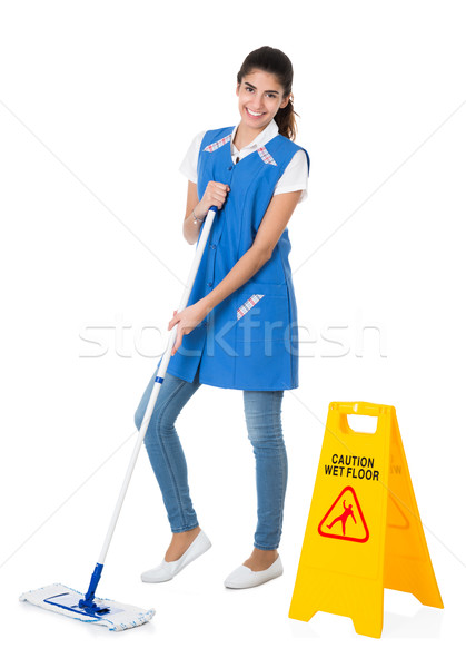 Happy Janitor Mopping By Caution Wet Floor Sign Stock photo © AndreyPopov
