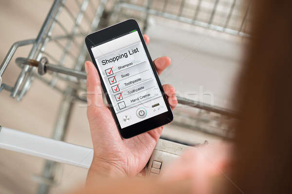 Woman Checking Shopping List On Smartphone In Supermarket Stock photo © AndreyPopov