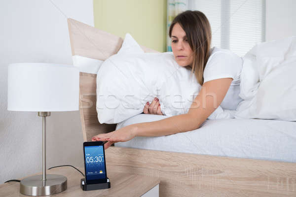 Woman On Bed Snoozing Alarm On Mobile Phone Stock photo © AndreyPopov