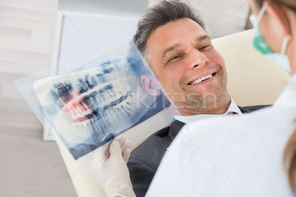 Dentist With Teeth X-ray In Front Of Businessman Stock photo © AndreyPopov