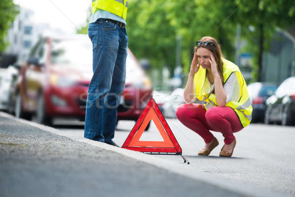 Woman Crouching Near Triangular Warning Sign Stock photo © AndreyPopov