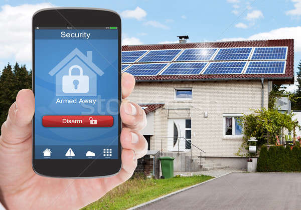 Person Holding Mobile Phone With Security System Stock photo © AndreyPopov