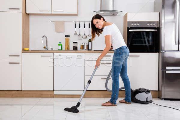 Kadın elektrikli süpürge temizlemek zemin genç mutlu Stok fotoğraf © AndreyPopov