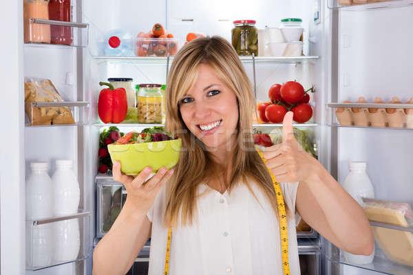 Femme manger salade réfrigérateur jeunes heureux Photo stock © AndreyPopov