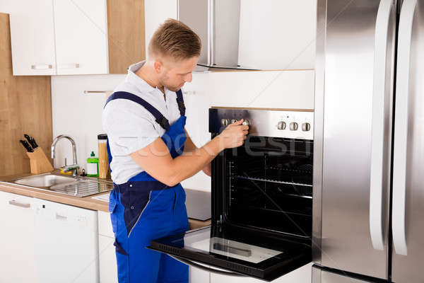 Technician Checking Oven In Kitchen Stock photo © AndreyPopov