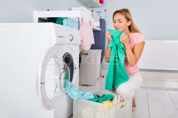 Woman Smelling Clothes After Washing Stock photo © AndreyPopov