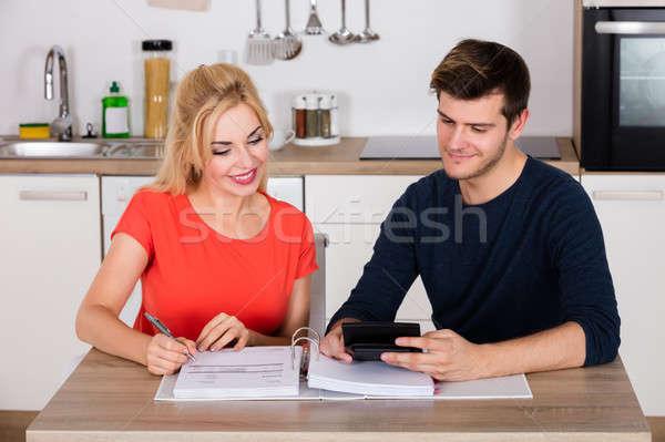 Happy Couple Calculating Invoice In Kitchen Stock photo © AndreyPopov