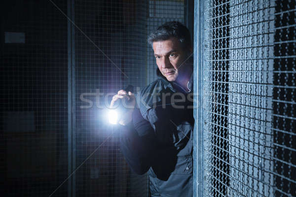 Security Guard Using Flashlight In The Warehouse Stock photo © AndreyPopov