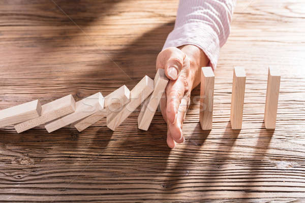 Female Hand Stopping The Domino From Falling Stock photo © AndreyPopov
