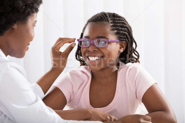 Smiling Girl Wearing Eyeglasses In Front Of Optometrist Stock photo © AndreyPopov