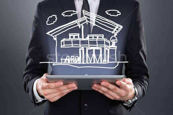 Businessman Showing Model Home Over Digital Tablet Stock photo © AndreyPopov