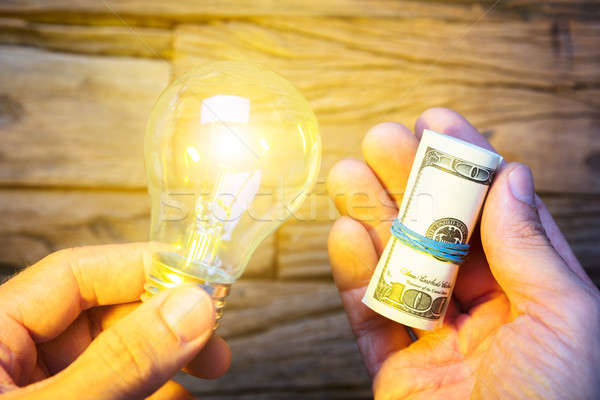 Hands Holding Dollar Notes And Lit Lightbulb Stock photo © AndreyPopov