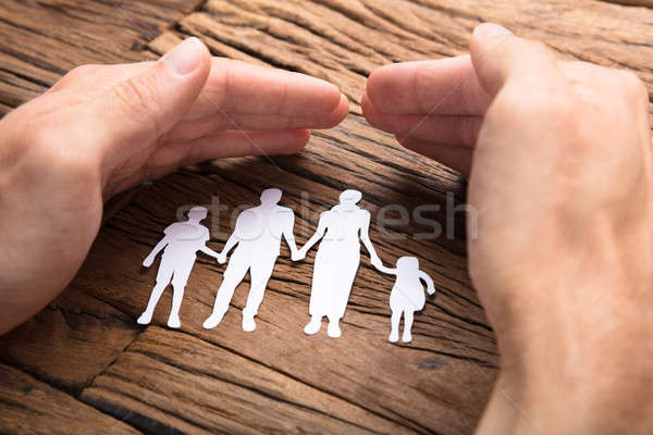Businessman Covering Paper Family At Wooden Table Stock photo © AndreyPopov