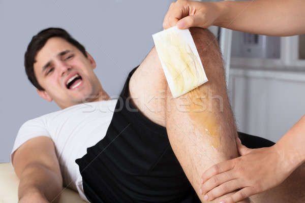 Therapist Waxing Man's Leg With Wax Strip Stock photo © AndreyPopov