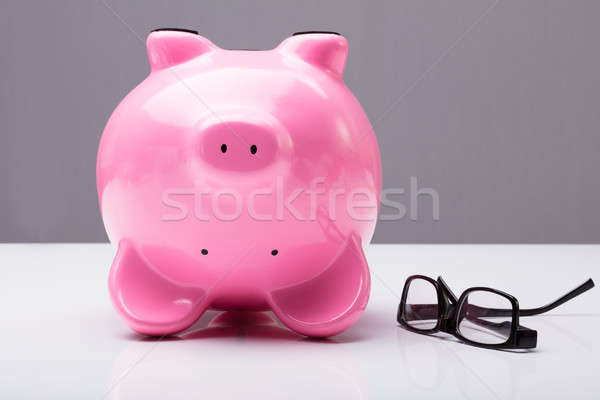 Upside Down Piggy Bank On Table With Eye Glasses Stock photo © AndreyPopov