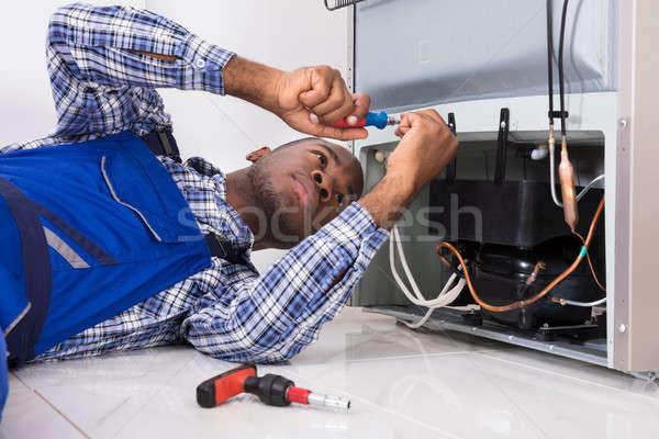 Homme travail frigo tournevis jeunes maison Photo stock © AndreyPopov