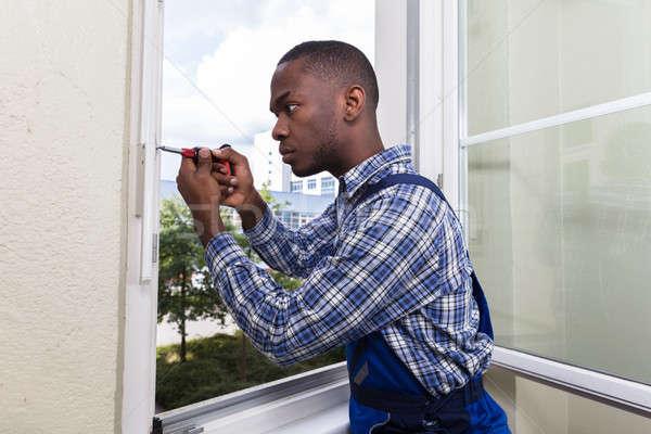 Handyman In Uniform Fixing Glass Window Stock photo © AndreyPopov