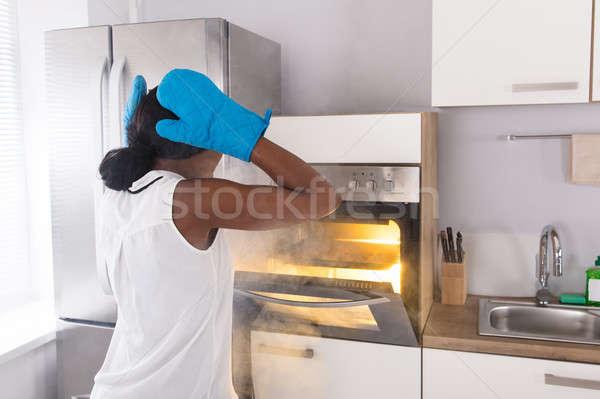 Megrémült nő néz sütik sütő füst Stock fotó © AndreyPopov