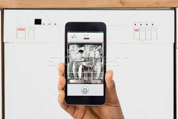 Close-up Of Woman's Hand Showing Dishwasher App Stock photo © AndreyPopov