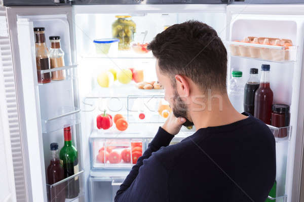 Confused Man Looking At Food In Refrigerator Stock photo © AndreyPopov