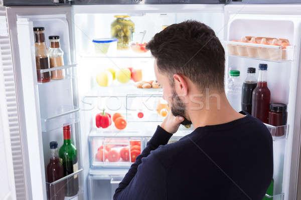Zavart férfi néz étel hűtőszekrény hátsó nézet Stock fotó © AndreyPopov