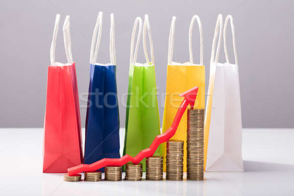 Stacked Coins In Front Of Multi Colored Shopping Bags Stock photo © AndreyPopov