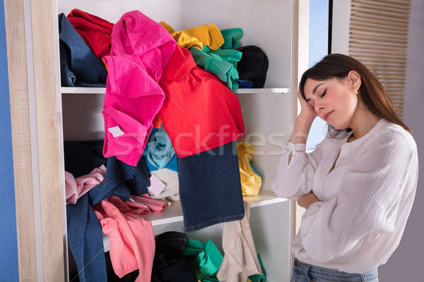 Woman Sleeping Near Messy Clothes On Shelf Stock photo © AndreyPopov