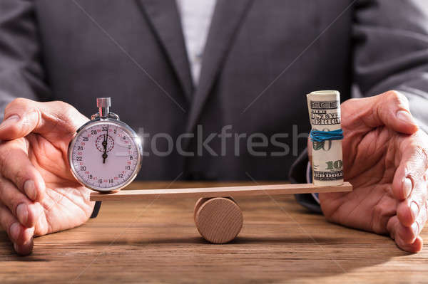 Businessperson Balancing Stopwatch And Rolled Up Banknotes Stock photo © AndreyPopov