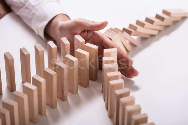 Businessperson Stopping Wooden Blocks From Falling Stock photo © AndreyPopov