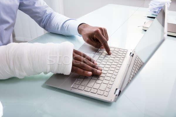 Businessman With Bandage Hand Using Laptop Stock photo © AndreyPopov