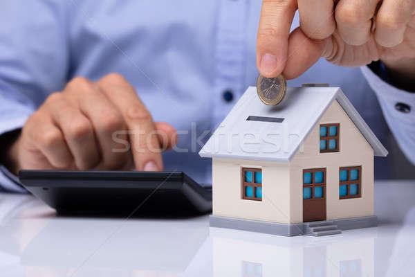Stock fotó: Személy · érme · ház · persely · számológép · üzlet