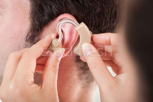 Person Adjusting Hearing Aid Stock photo © AndreyPopov