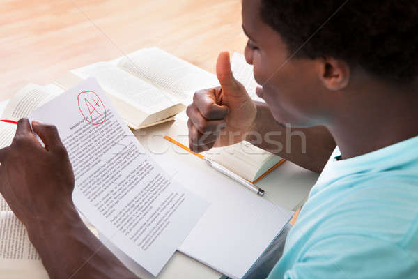 Young Man Showing A Paper With Grade A Plus Stock photo © AndreyPopov