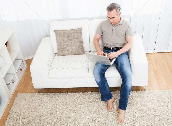 Dojrzały mężczyzna za pomocą laptopa posiedzenia kanapie komputera Zdjęcia stock © AndreyPopov
